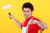 A painter holding a paint roller — Stock Photo