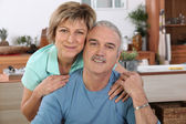 Mature couple sitting in the kitchen — Stock Photo