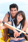 Young couple in a paddle boat — Stock Photo