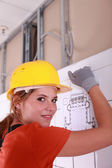 A female electrician installing a wire board. — Stock Photo
