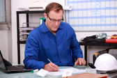 Builder working on paperwork in an office — Stock Photo