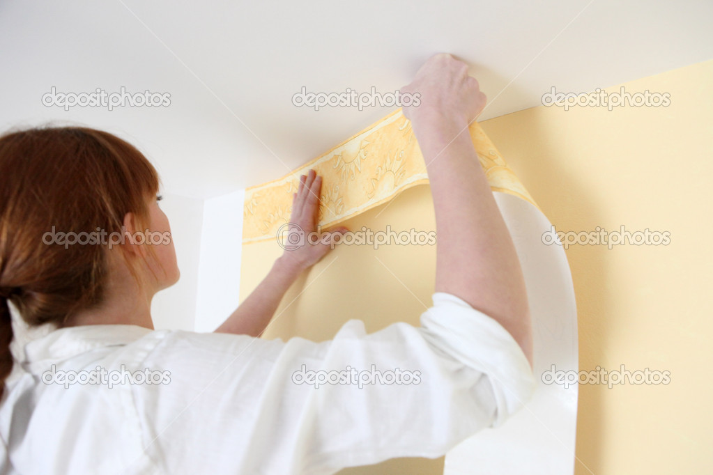 Woman putting up a wallpaper border — Stock Photo #8032581