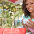 Stock Photo: Woman with a shopping bag drinking tea outside