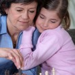 A grandmother and her granddaughter playing chess. — Stock Photo