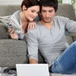 Couple sat on couch with newspaper and laptop — Foto de stock #8048898