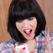 Brunette shouting angrily at phone — Stock Photo