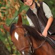 Young girl horseriding through the forest - Stock Photo