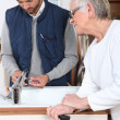 Young man fixing faucet for older woman — Stock Photo #8049473