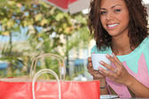 Woman with a shopping bag drinking tea outside — Stock Photo