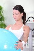 Mujer joven haciendo ejercicios con pelota suiza — Foto de Stock