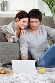 Couple sat on couch with newspaper and laptop — Stock Photo