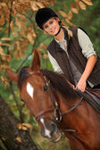 Young girl horseriding through the forest — Stock Photo