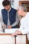 Ung man fastställande kran för äldre kvinna — Stockfoto