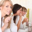 Three young women cleaning their teeth — Stock Photo