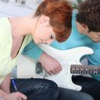 A woman writing and her boyfriend playing guitar — ストック写真