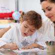 Teacher watching her pupil colouring a drawing - Stock Photo
