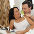 Couple in bed reading magazine — Stock Photo