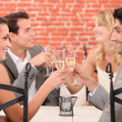 Two well dressed couples toasting at restaurant — Stock Photo #8050918