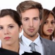 Closeup of the faces of a group of serious young executives and their older — Stock Photo #8051531