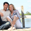 Mid age couple seated on a pontoon near a lake — Stock Photo #8051721