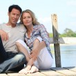 Stock Photo: Mid age couple seated on pontoon near lake
