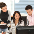 Three colleagues gathered around computer screen — Stock Photo #8051947