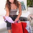 Woman sat looking through shopping bags — Stock Photo
