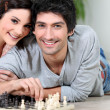 Attractive couple playing chess - Stock Photo