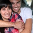 Happy couple embracing in car - Stock Photo