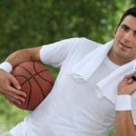 Angled shot of man with basketball and kit bag — Stock Photo