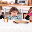 Three children eating crepes - Stock Photo