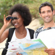 Tourists looking a map and using binoculars - Stock Photo