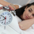 A woman stopping an alarm clock — Stock Photo #8054078