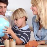 Happy family looking terrestrial globe — Stock Photo