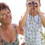 Little girl looking through binoculars — Stock Photo #8054934