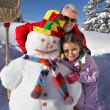 Father and daughter building snowman - Stock Photo