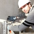 Builder cutting an outdoor pipe — Stock Photo