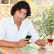 Stock Photo: Msitting at outdoor cafe table with cellphone and glass of rose