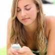 Teenage girl texting on the beach — Stock Photo
