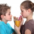 Two children sharing orange juice — Stock Photo