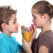Royalty-Free Stock Photo: Two children sharing orange juice