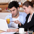 Couple having breakfast and working on a laptop — Stock Photo