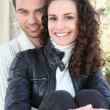 Young couple sat by wall - Foto Stock