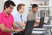 Estudantes que usam computadores portáteis — Fotografia Stock