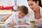 Teacher watching her pupil colouring a drawing — Foto Stock