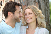Couple in love in front of a tree — Stock Photo
