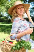 Woman smiling with straw hat and basket of vegetables. — Stock Photo