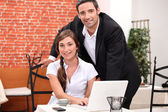 Couple in a restaurant working on a laptop — Stock Photo