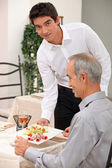 Young waiter serving an older customer — Stock Photo