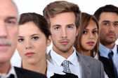 Closeup of the faces of a group of serious young executives and their older — Stock Photo